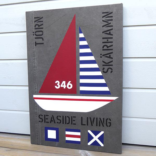 New England inspirerad tavla med segelbåt och signalflaggor samt texterna TJÖRN, SKÄRHAMN, SEASIDE LIVING