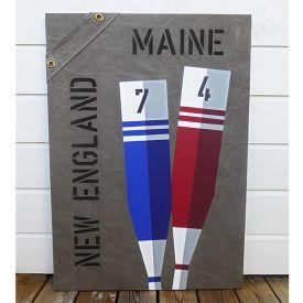 Tavla i marin stil med motiv av åror och texten Maine New England