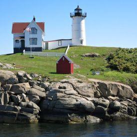 fyr på ö med klippor och vatten