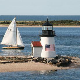 Amerikansk fyr från New England med segelbåt, strand och vatten