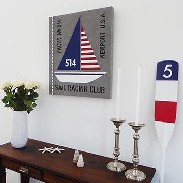 Tavla med segelbåt målad på sliten canvas och riktig tross samt paddel som passar utmärkt i New England miljöer.